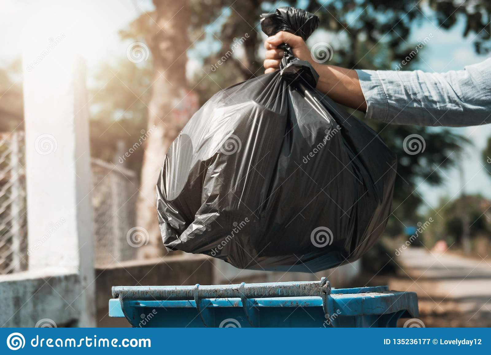 De de holdingsvuilniszak van de vrouwenhand bracht aan afval aan