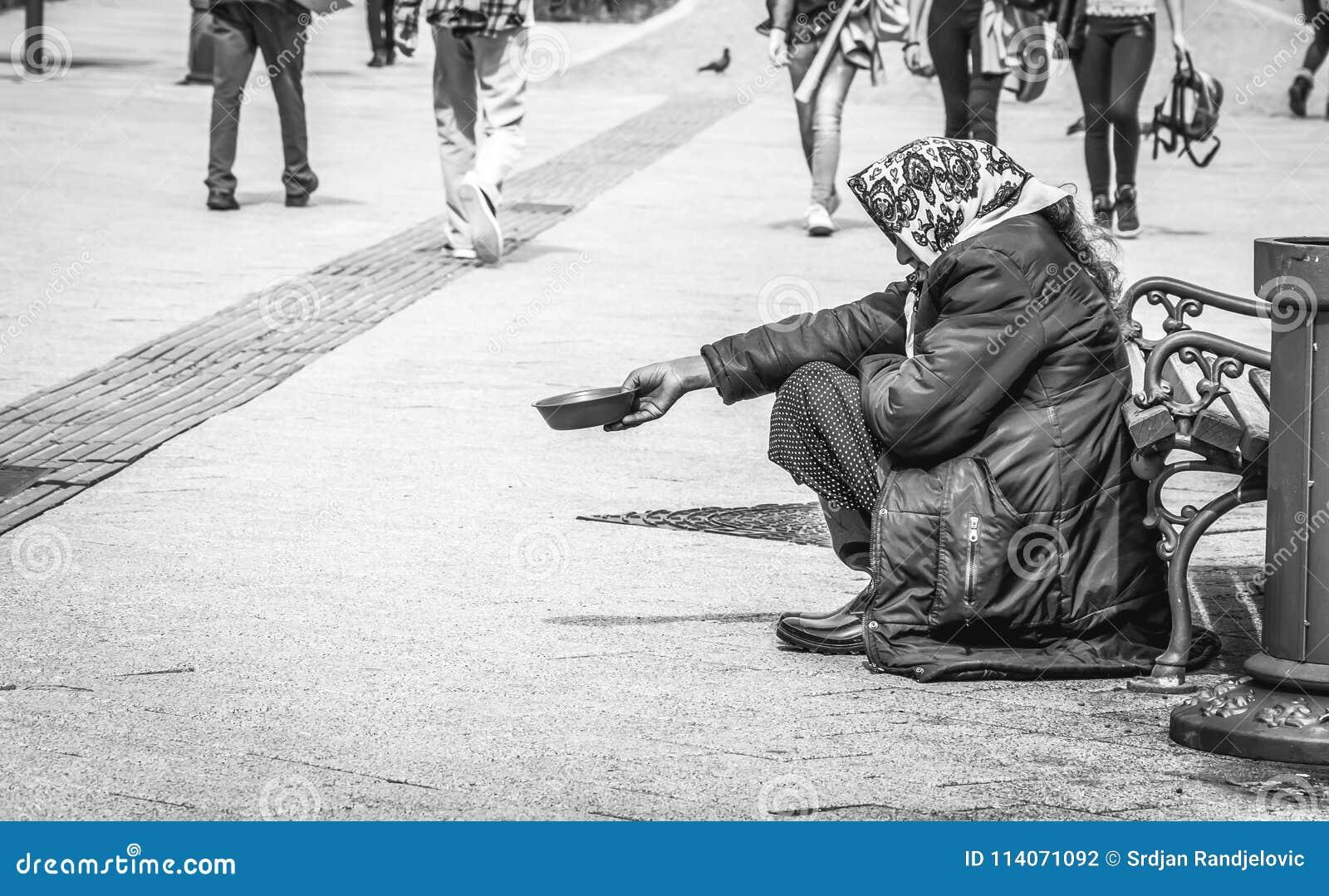 De hongerige dakloze bedelaarsvrouw bedelt voor geld op de stedelijke straat in de stad van mensen die, sociaal documentair conce