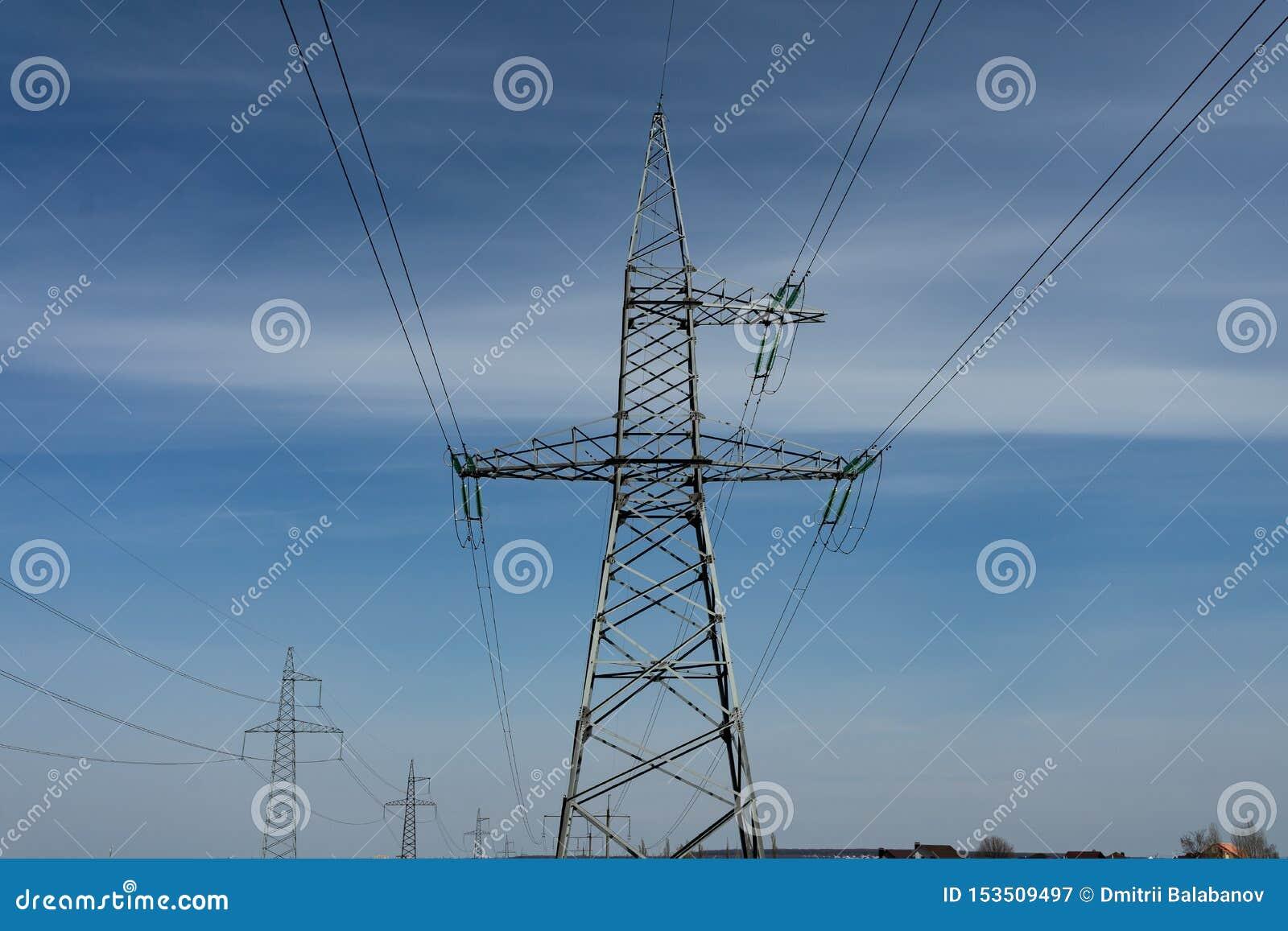 De hoogspanningslijnen en de machtspylonen op een zonnige dag met cirrus betrekken in de blauwe hemel