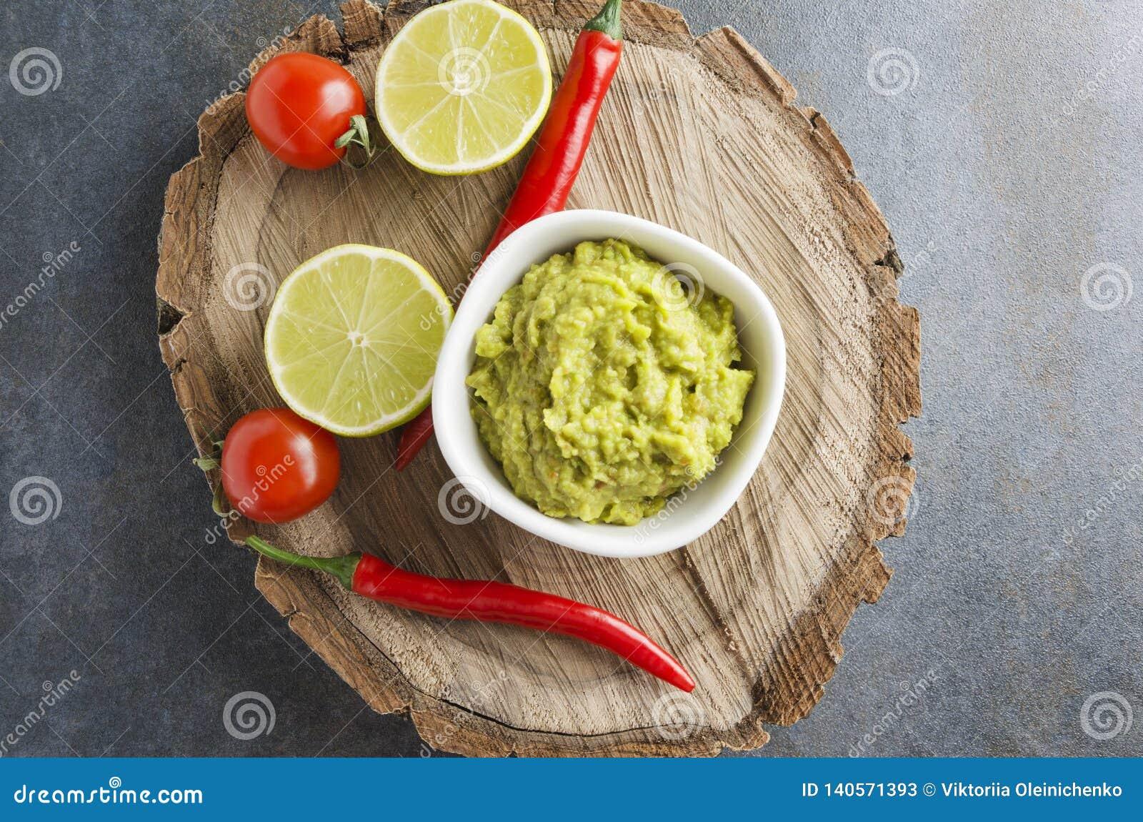 De hoogste mening van heerlijke verse guacamole met Spaanse peperspeper, kalk, kersentomaten diende op houten dienblad