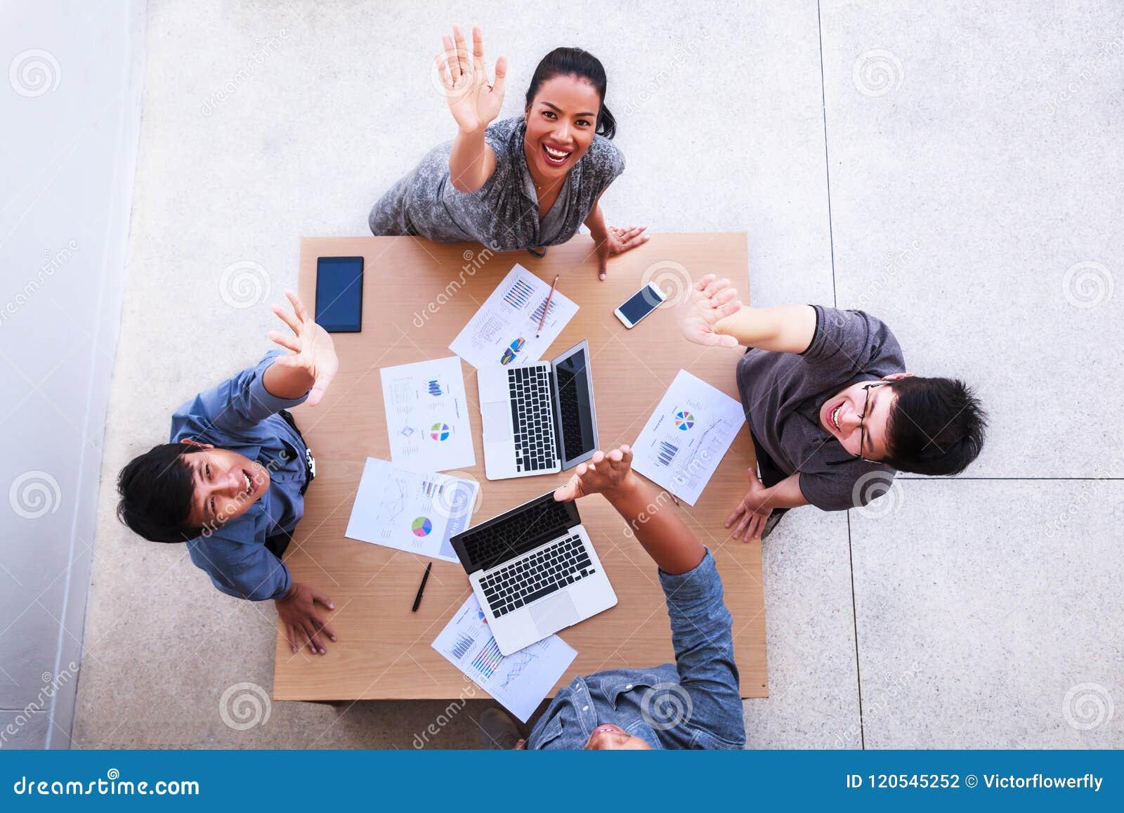 De hoogste mening van zakenlieden en de onderneemster vieren over lijst in een vergadering met exemplaarruimte op mobiel kantoor