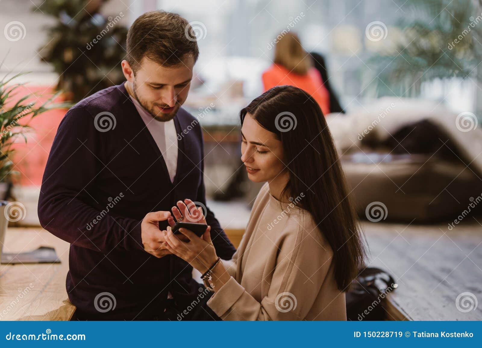 De houdende van kerel en het meisje gekleed in sweaters en jeans zitten bij de lijst in de koffie en bekijken de mobiele telefoon