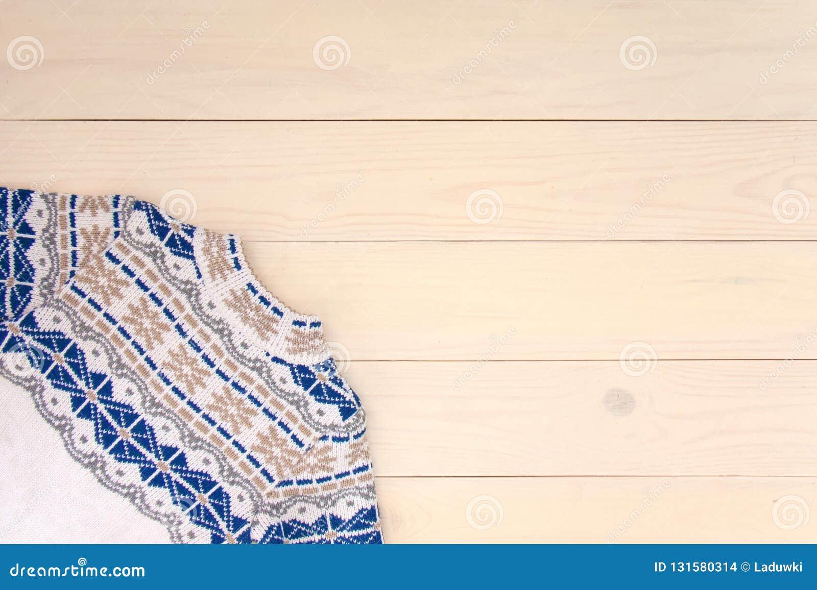 De houten achtergrond van de Kerstmisdecoratie met gebreide wolsweater met jacquardornament in witte blauw en beige Kaartconcept
