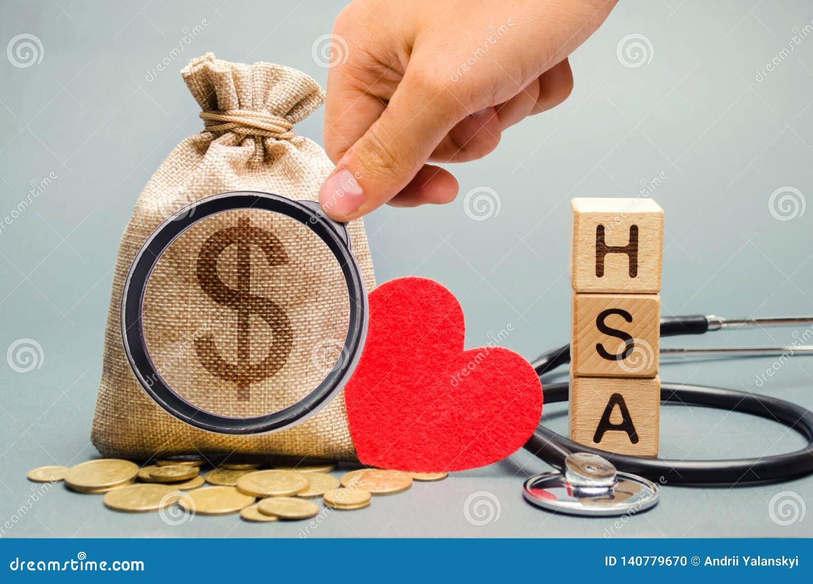 De houten blokken met het woord HEBBEN en de geldzak met stethoscoop Gezondheidsspaarrekening Vertragingen en wapens De verzekeri