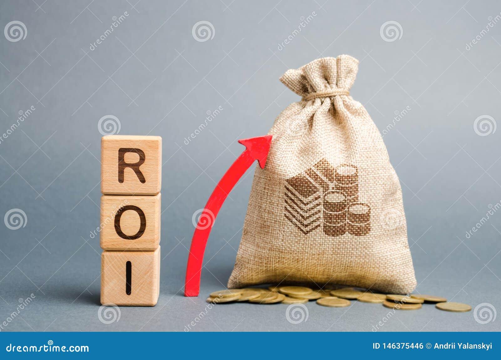 De houten blokken met het woord ROI en de omhooggaande pijl met het geld doen in zakken Hoog niveau van bedrijfsrentabiliteit Ren