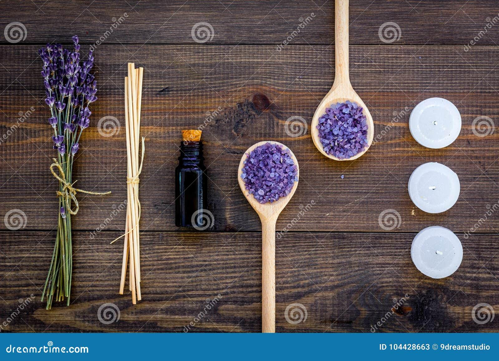 De huidzorg en ontspant Schoonheidsmiddelen en aromatherapy concept Het zout en de olie van het lavendelkuuroord op donkere houte