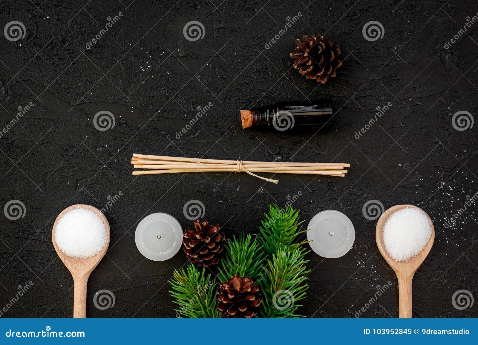 De huidzorg en ontspant Schoonheidsmiddelen en aromatherapy concept Pine spa zout, olie, nette tak en pinecones op zwarte