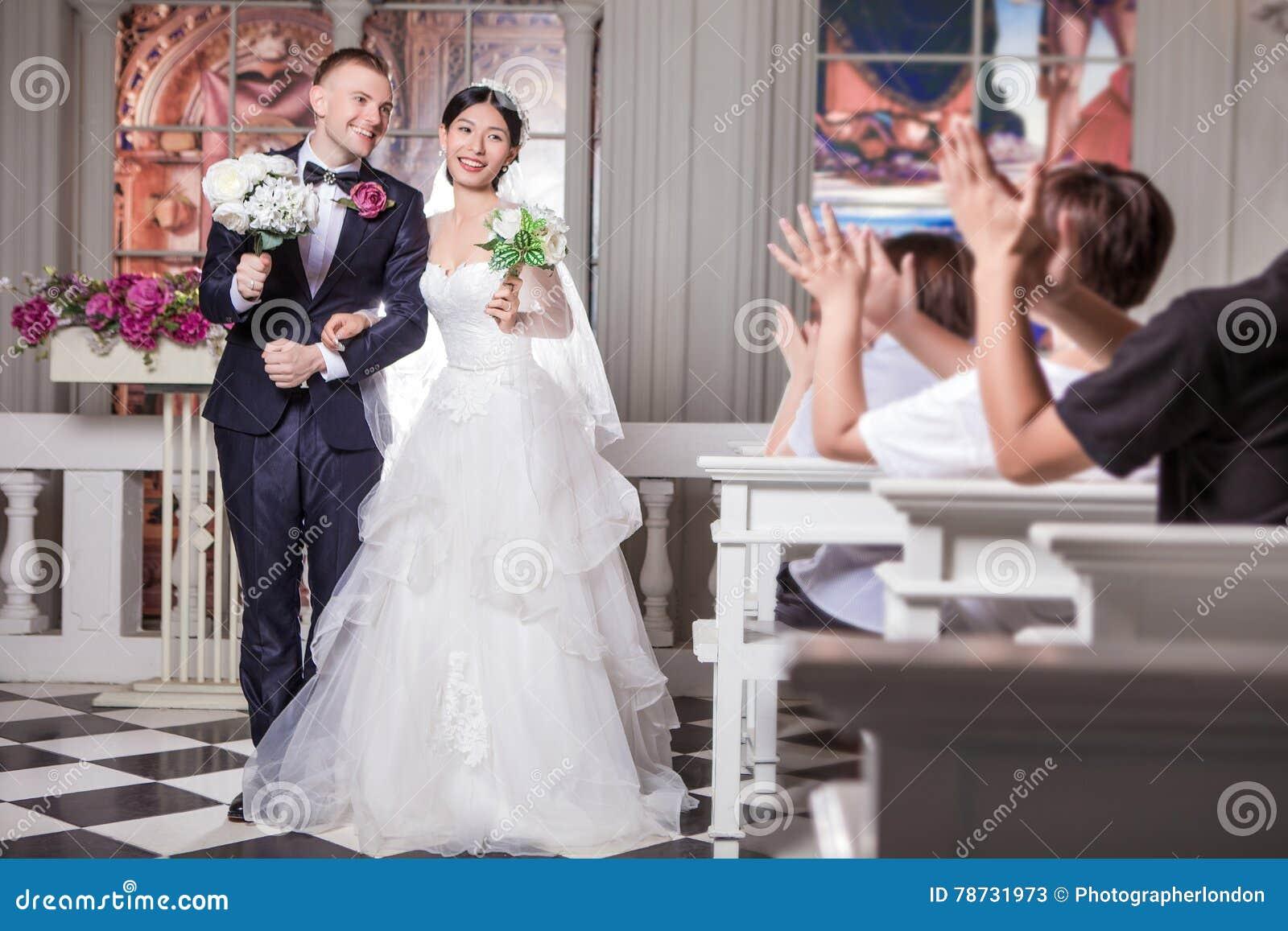 De huwelijksgasten die voor jonggehuwde toejuichen koppelen holdingsbloemen in kerk