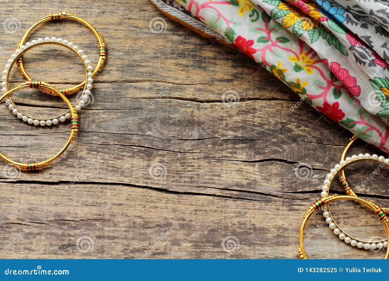 De Indische juwelenarmbanden en de bloemen etnische stof liggen op een houten achtergrond