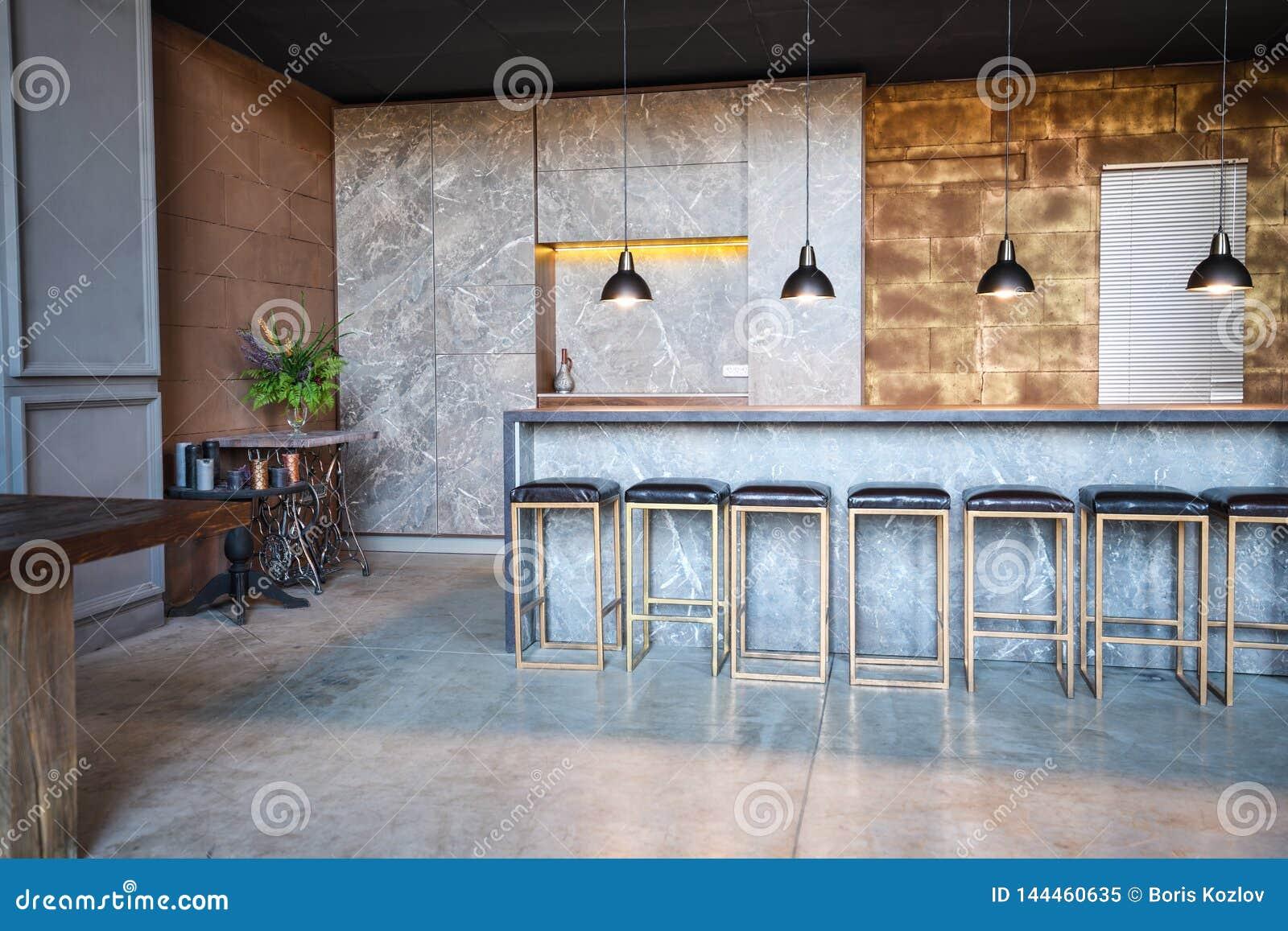 De industriële stijl van de zolderbar De ruimte heeft heel wat stoelen bij de bar, vier overhangende lampen