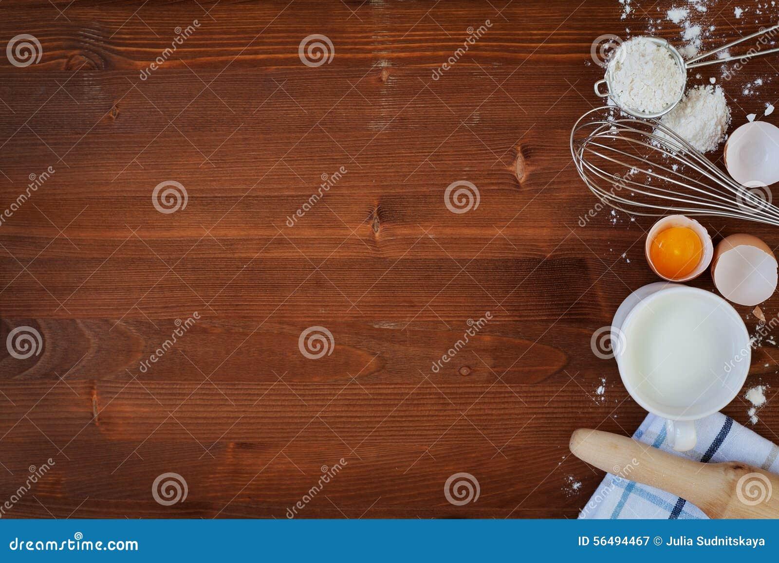 De ingrediënten voor bakseldeeg met inbegrip van bloem, eieren, melk, zwaaien en deegrol op houten rustieke achtergrond