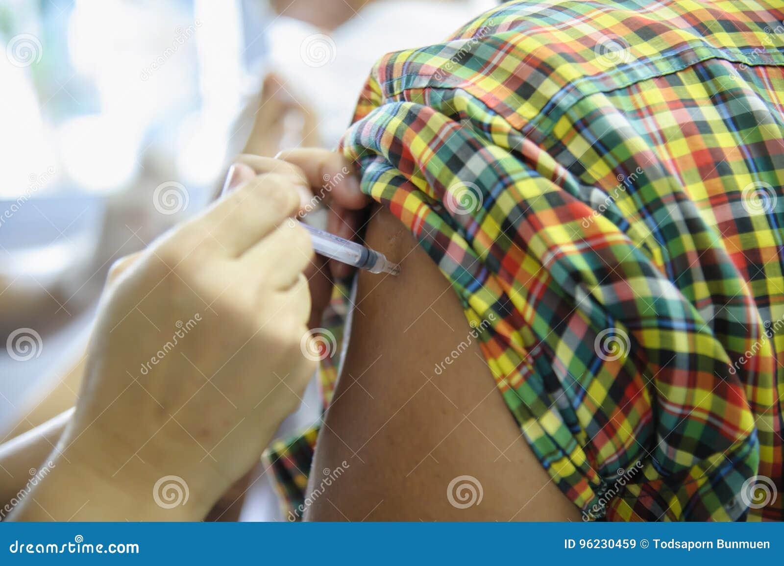 De injectie van het immuniseringsvaccin, arts spuit vaccin aan geduldig wapen in
