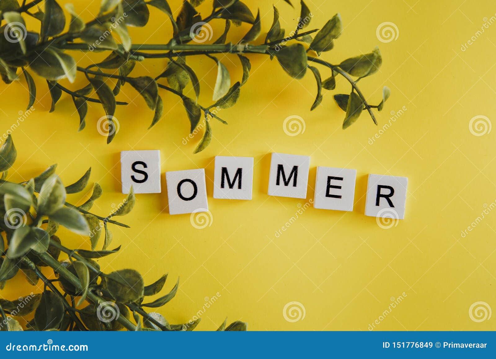 De inschrijving sommer in het Duits op de brieven van het toetsenbord op een gele achtergrond met bloemen