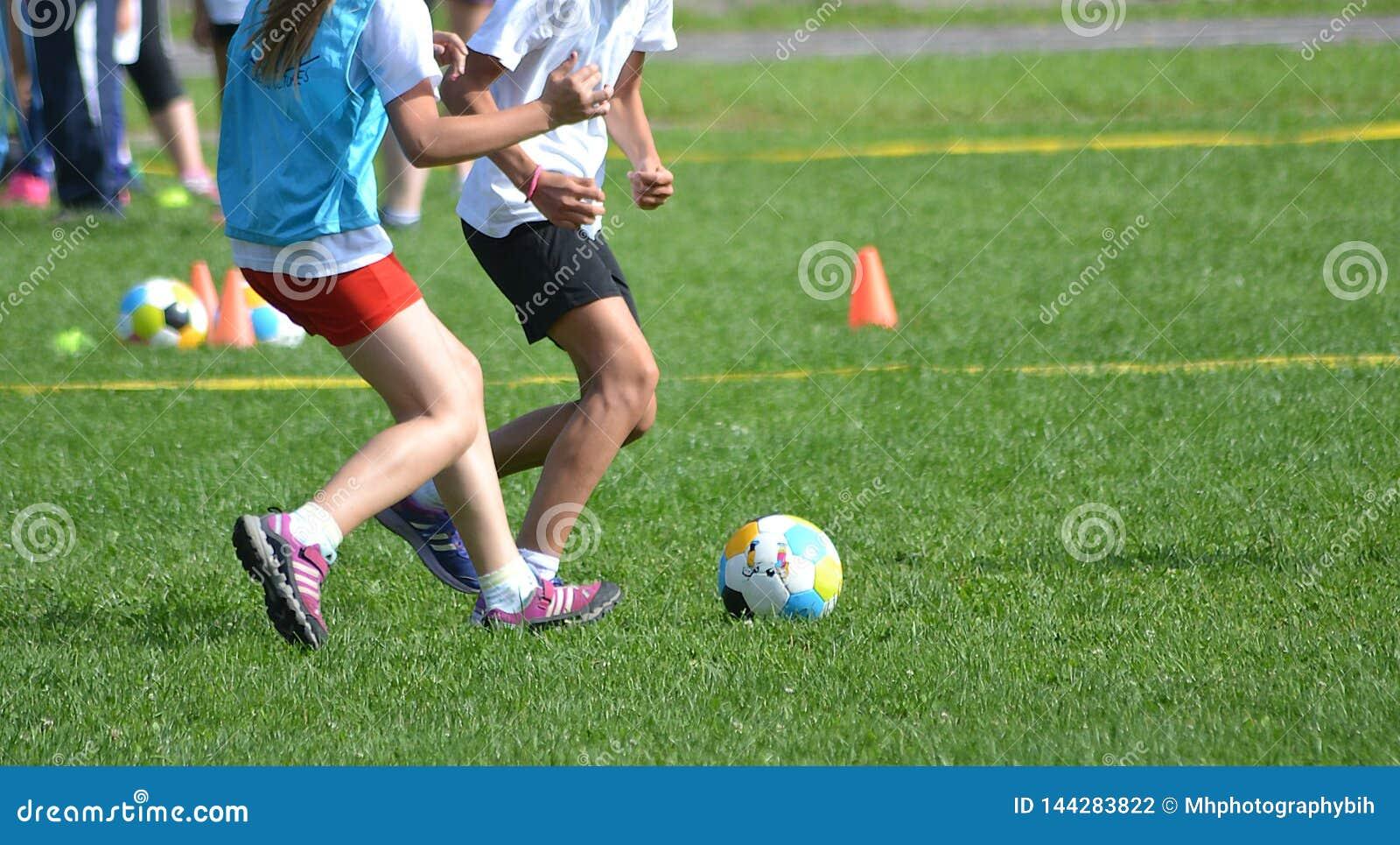 De jong geitjemeisjes spelen voetbal