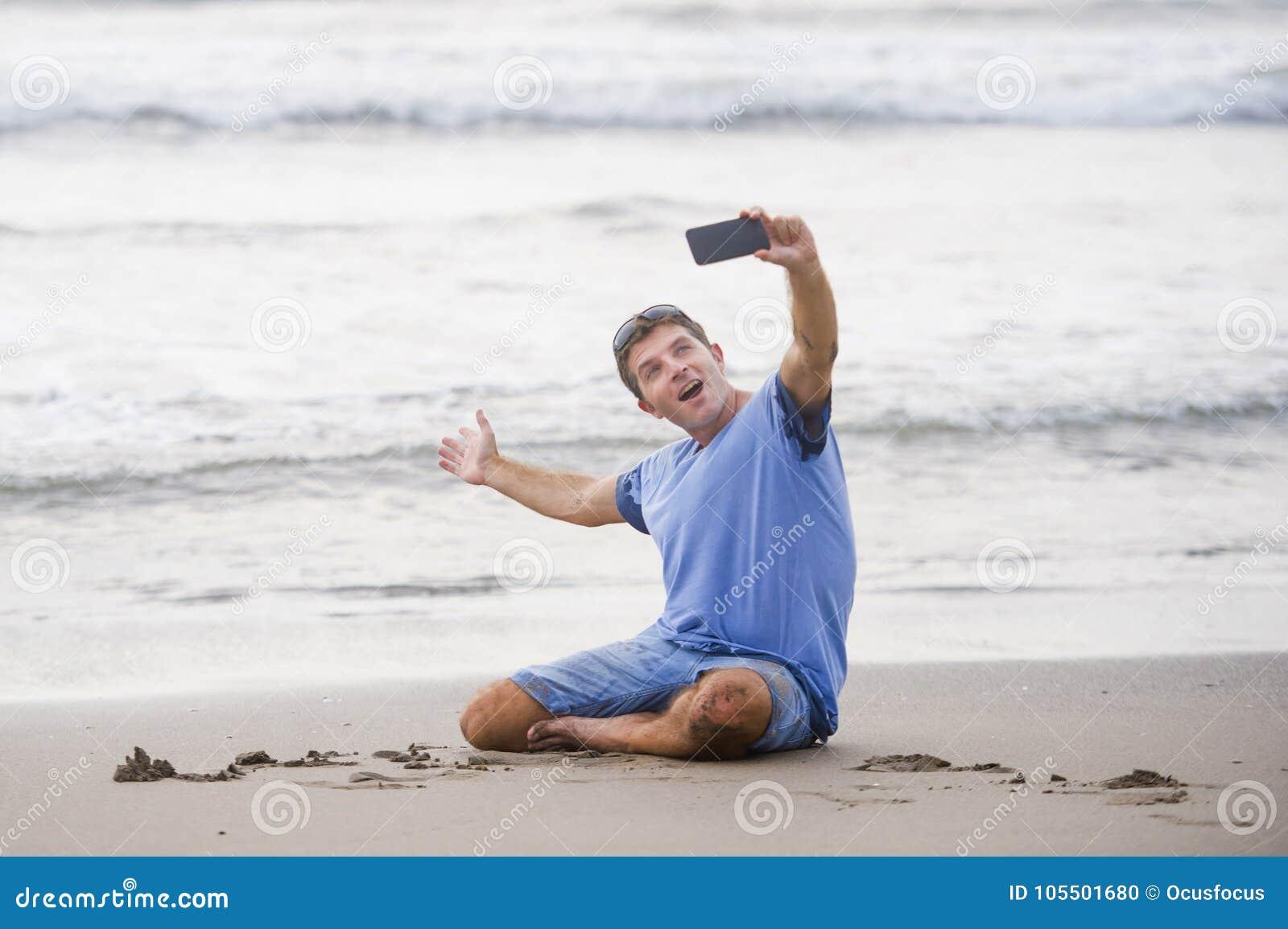 De jonge aantrekkelijke en gelukkige Kaukasische jaren  30mens die pret hebben bij Aziatisch strand die selfie stelt met mobiele
