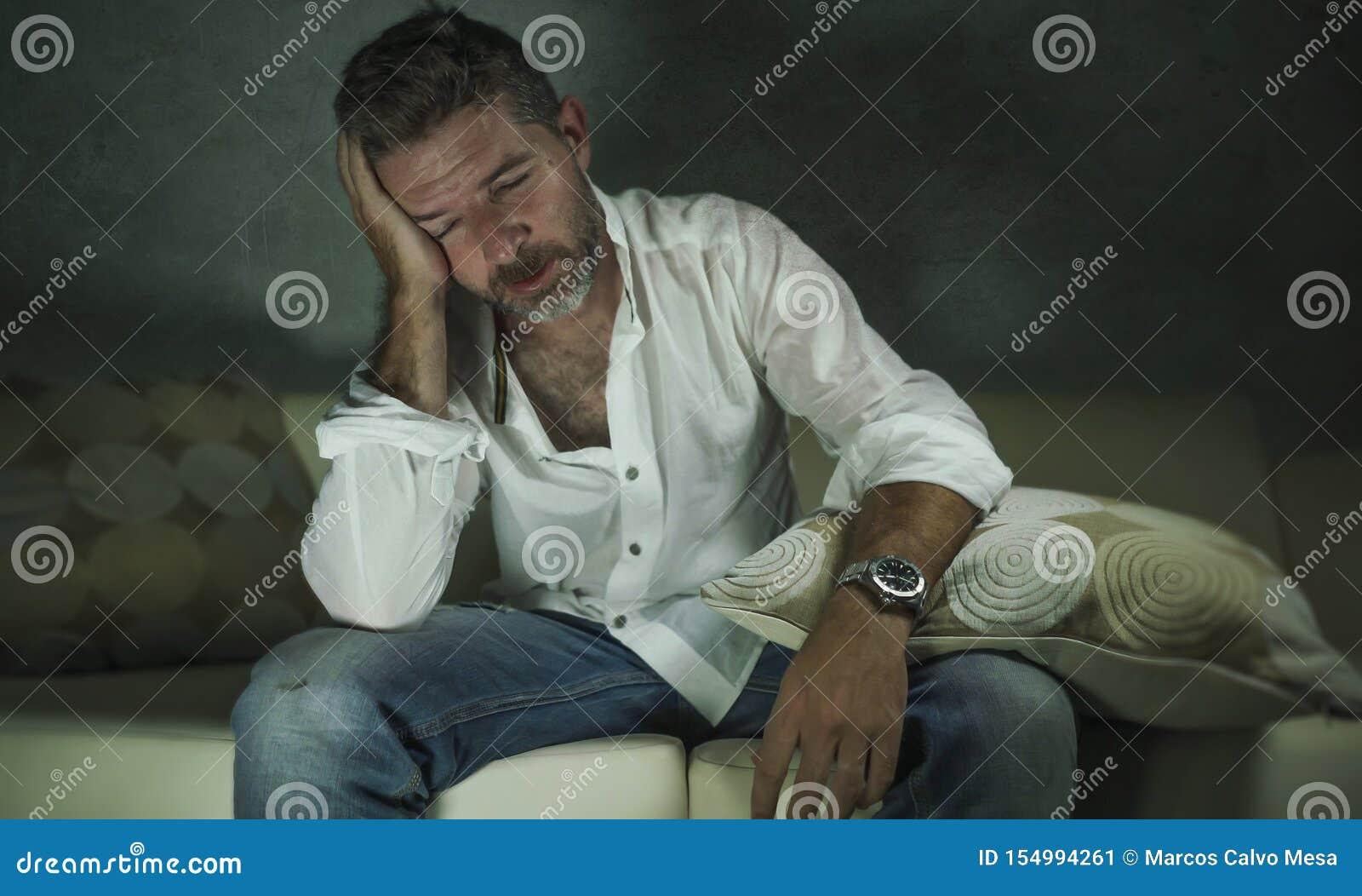 De jonge aantrekkelijke gedeprimeerde en droevige schaduwrijke mens gaat liggen thuis schreeuwen verloren in pijn en wanhoopt lij