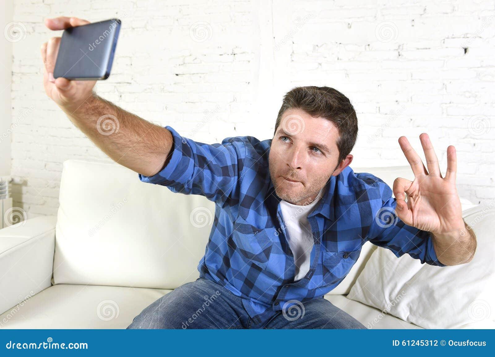 De jonge aantrekkelijke jaren  30mens die selfie stelt of zelfvideo met mobiele telefoon thuis zittend bij laag gelukkig glimlach