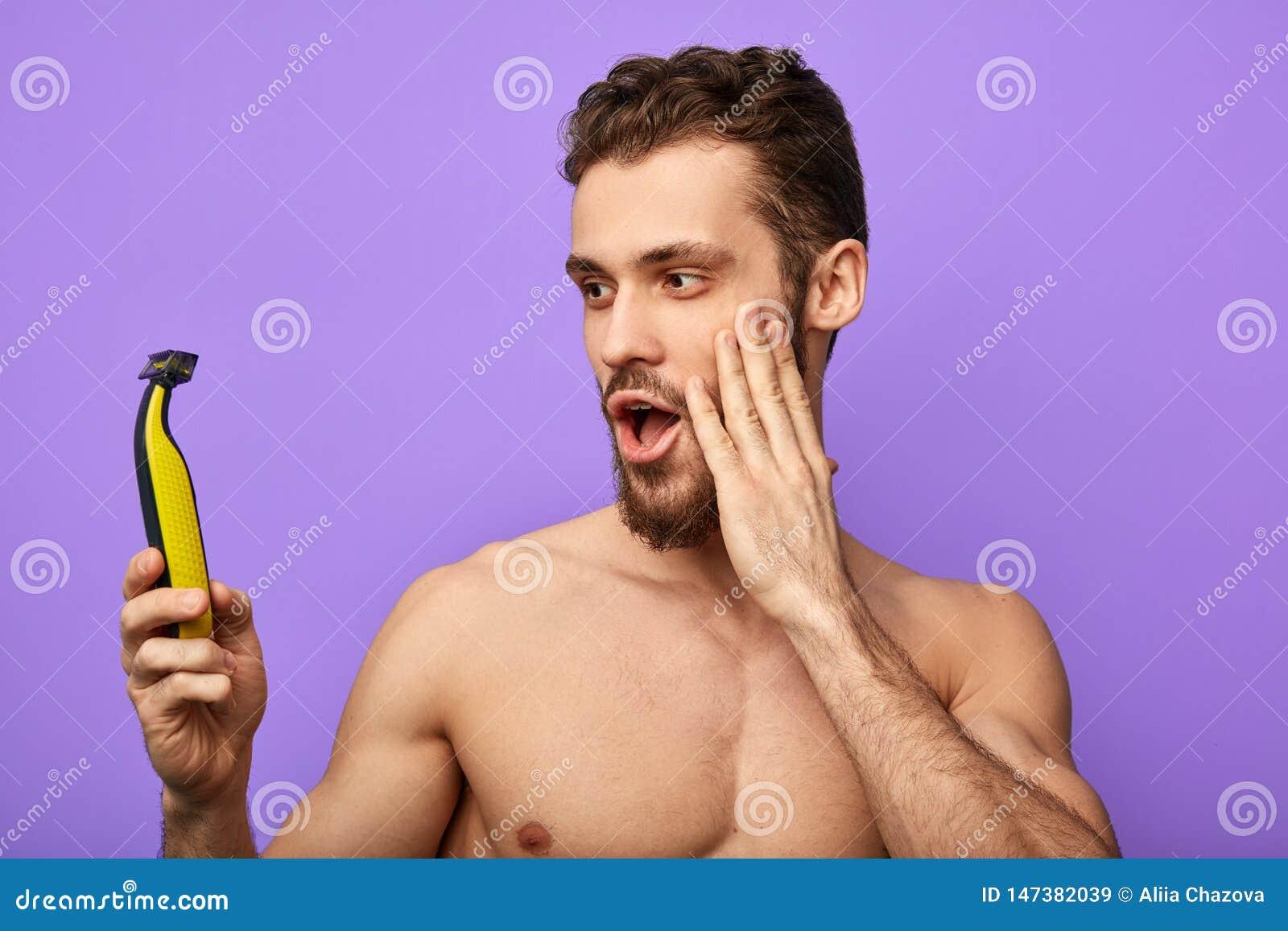 De jonge aantrekkelijke mens is gelukkig om positief effect tijdens het scheren te hebben