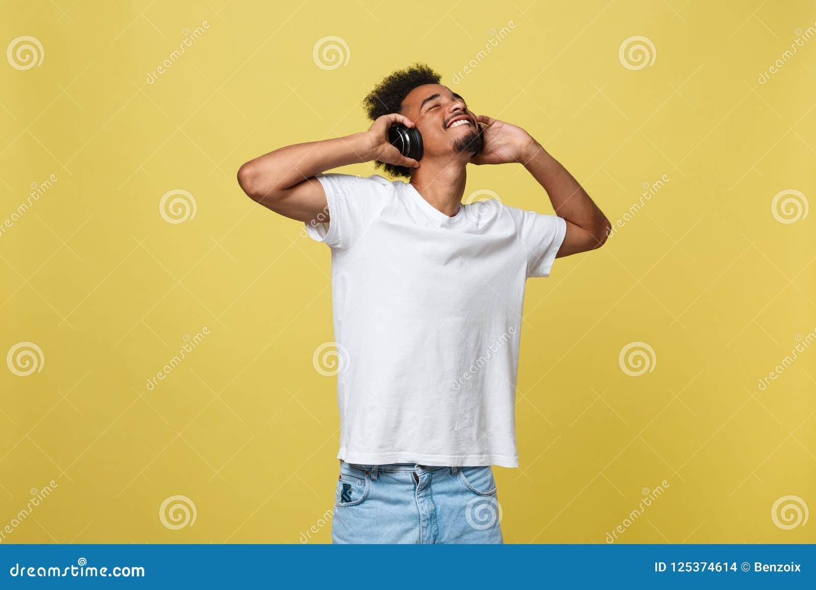 De jonge Afrikaanse Amerikaanse mens die hoofdtelefoon dragen en geniet van muziek over gele gouden Achtergrond