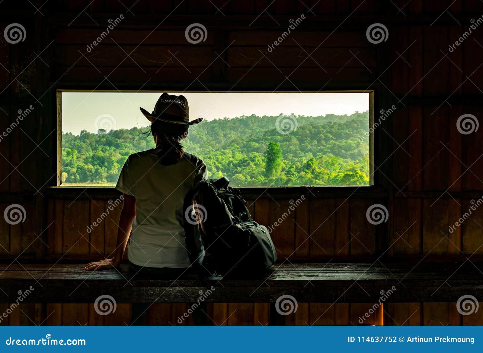 De jonge Aziatische vrouw draagt de hoed zit op houten bank en het letten op mooie mening van tropisch bos bij de toren van de he
