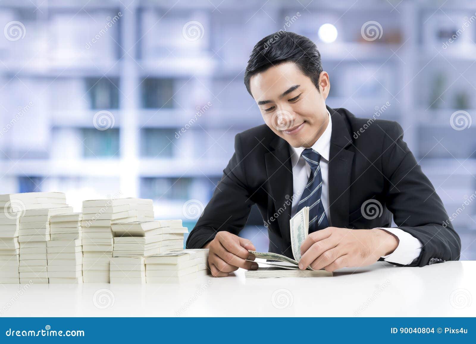 De jonge bankier telt bankbiljetten op de achtergrond van het bankbureau