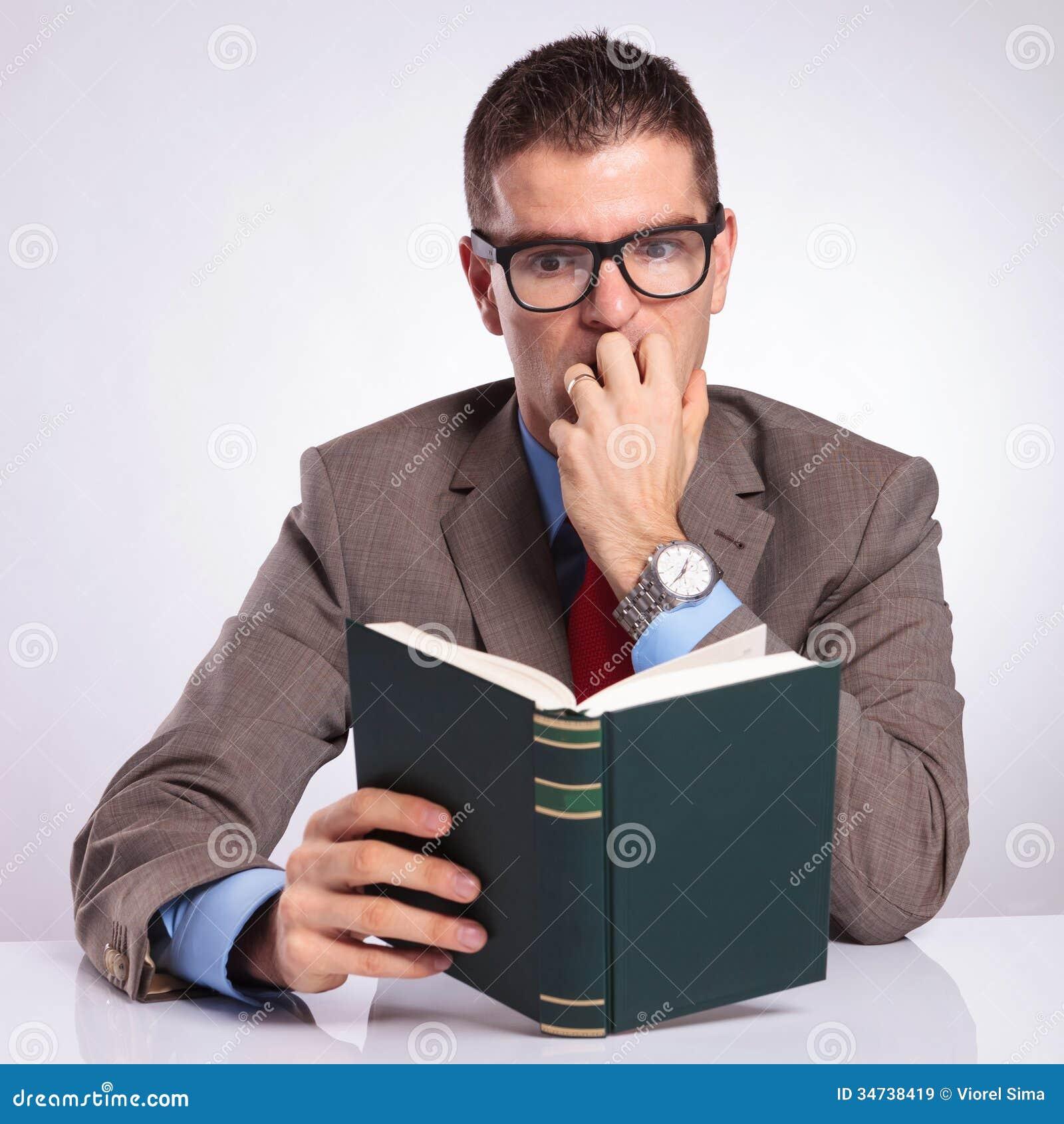 De jonge bedrijfsmens leest een eng boek