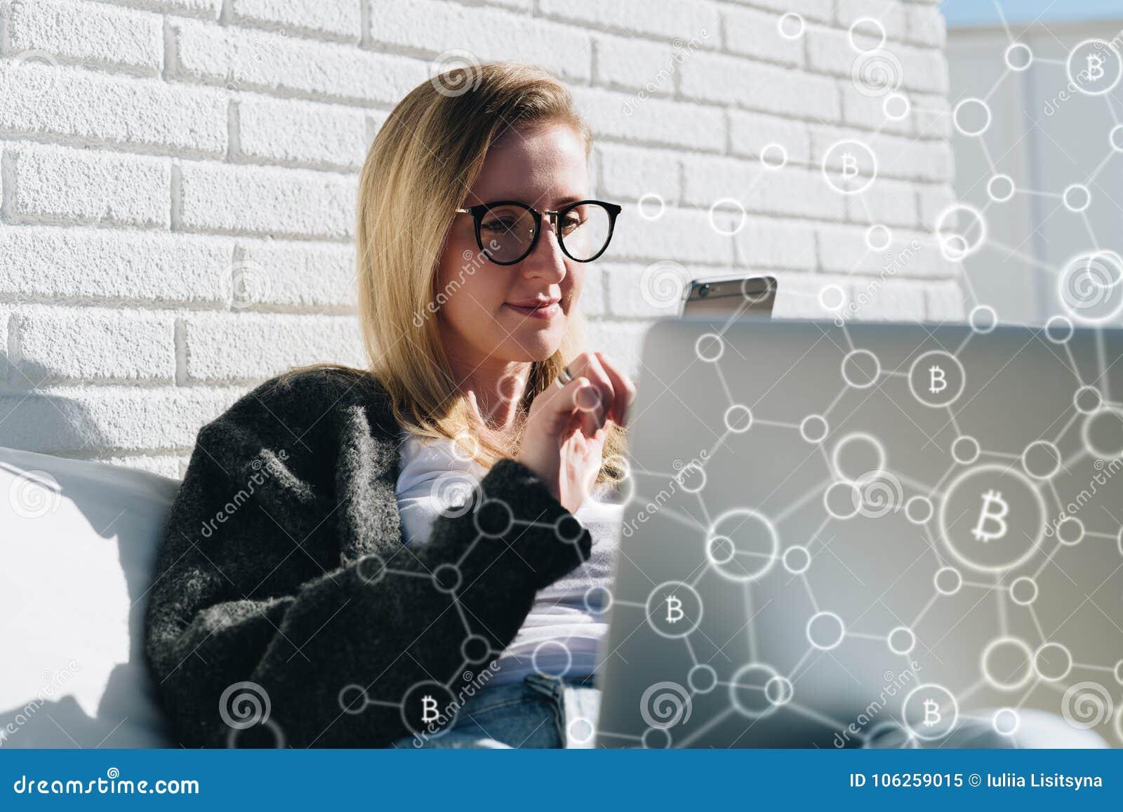 De jonge bedrijfsvrouw in glazen zit bij laptop en gebruikt smartphone In voorgrondinfographics, bitcoin pictogrammen