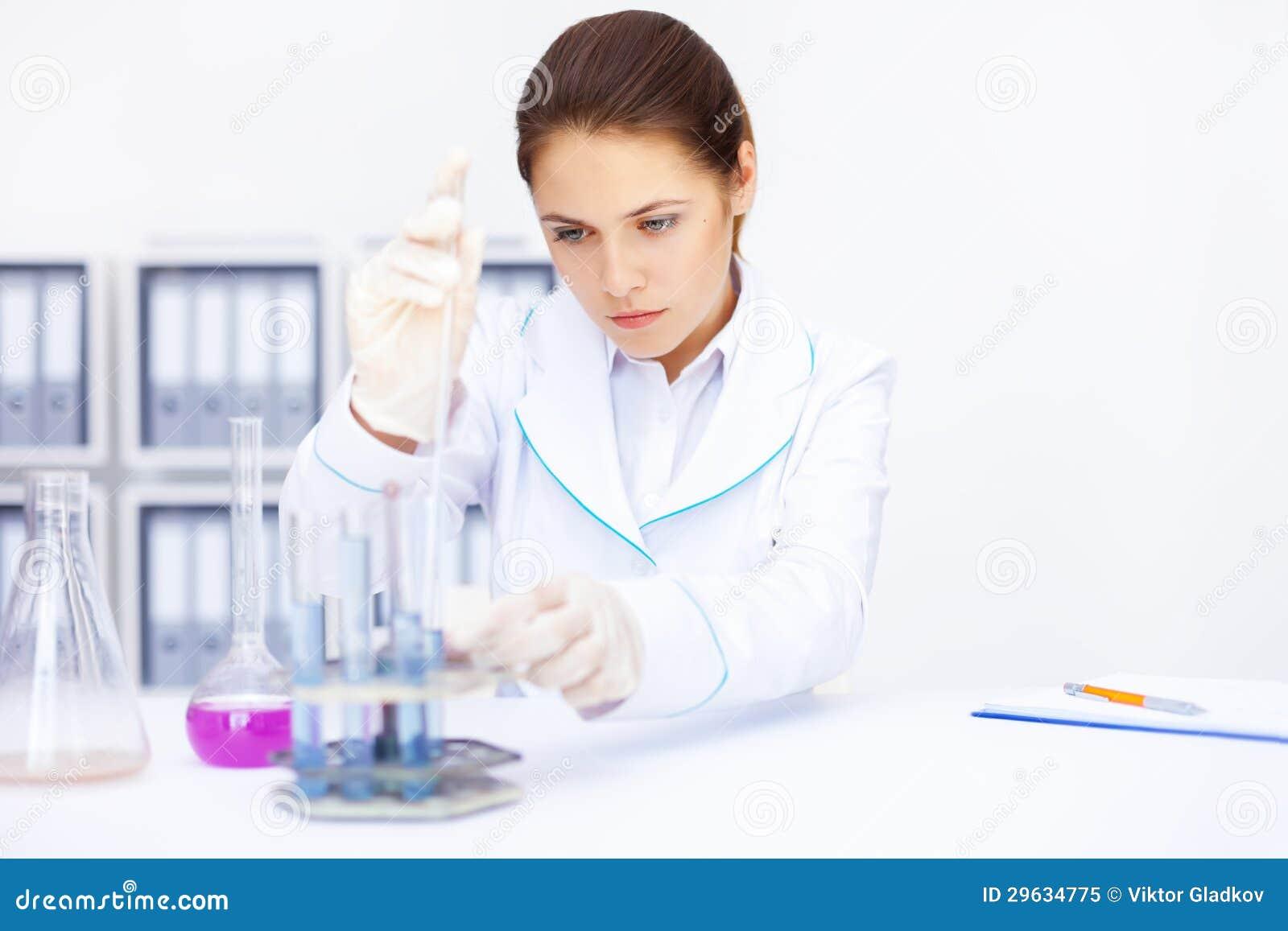 De jonge chemische vrouwelijke onderzoeker met flesjes en flessen maakt som