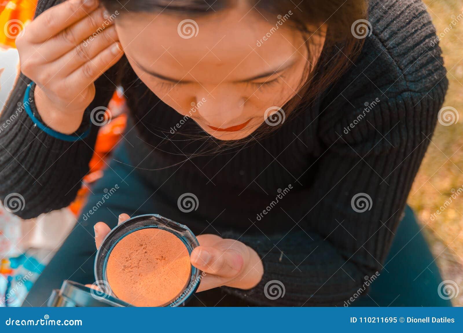 De jonge dame die op haar zetten maakt omhoog het kijken op een zakspiegel
