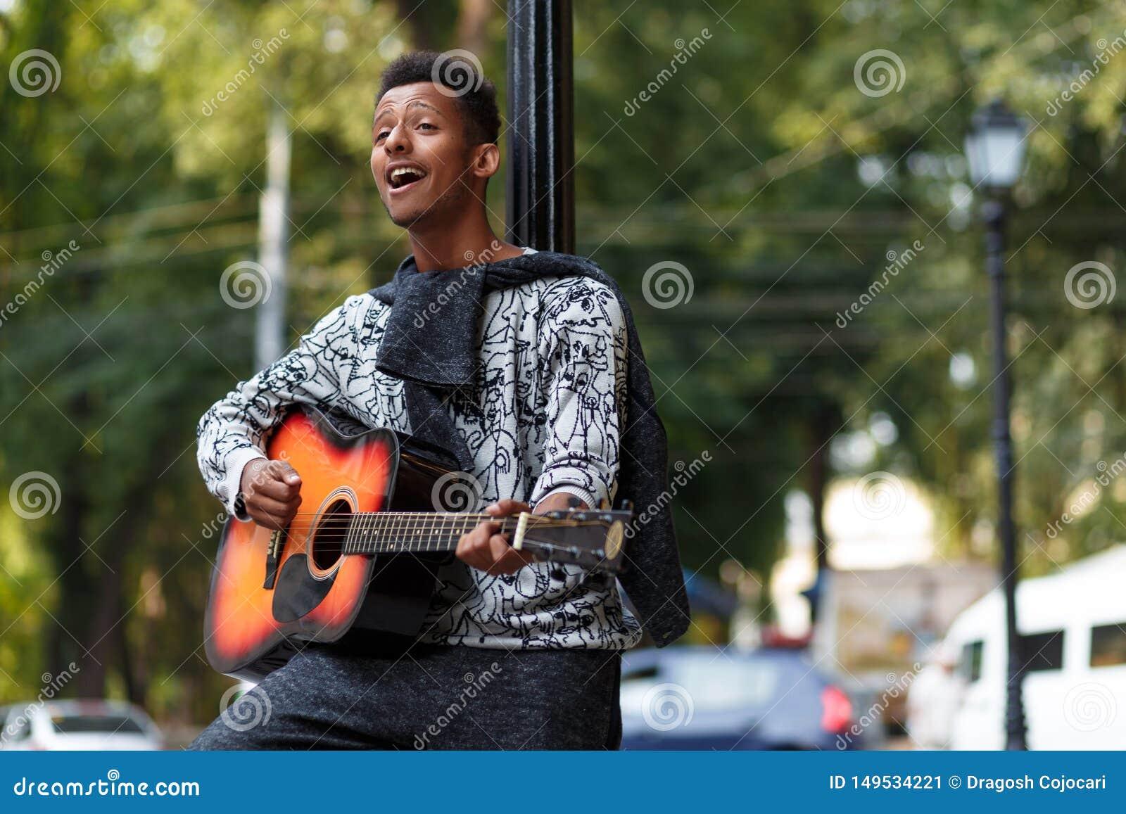De jonge die musicus op gitaar wordt gespeeld, zingt een lied in zonnige dag, op een vage straatachtergrond