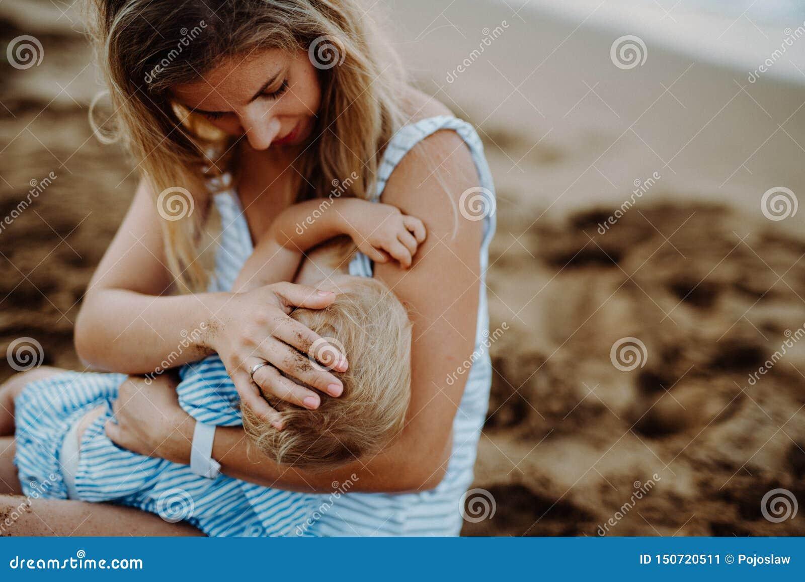De jonge dochter van de moeder breasfeeding peuter op strand op de zomervakantie