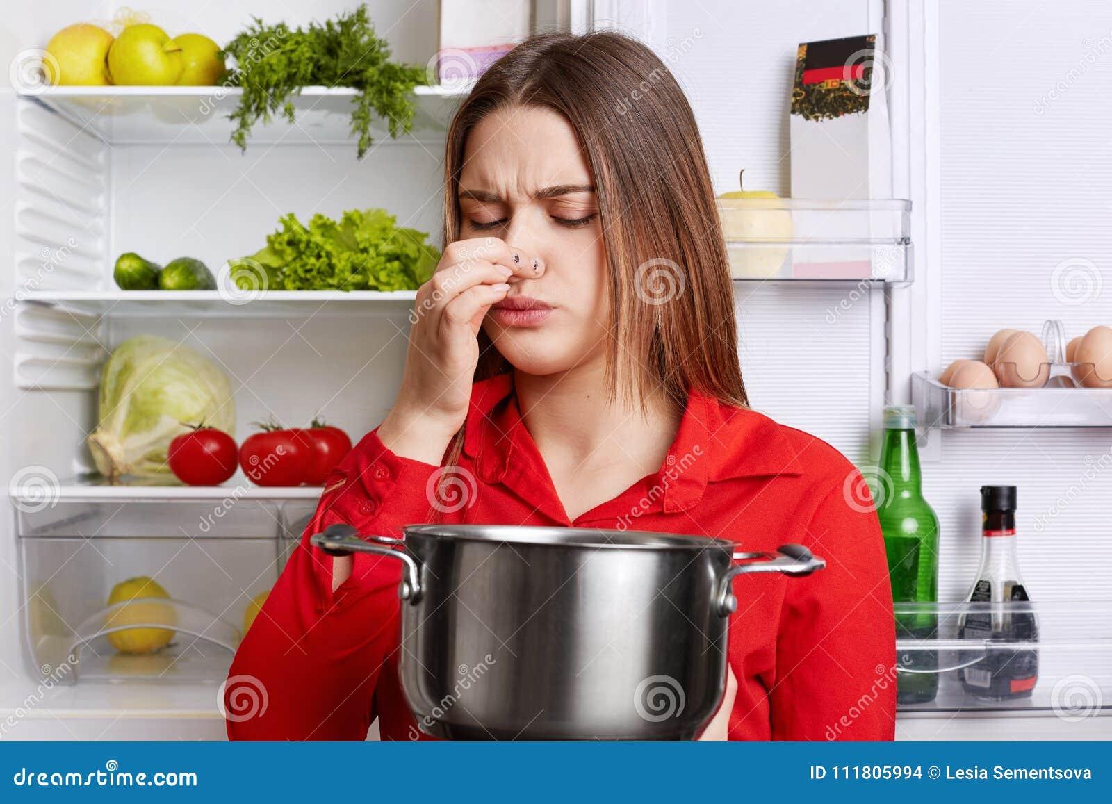 De jonge donkerbruine vrouw met ontstemde uitdrukking ruikt bedorven soep in hutspotpan, voelt thuis muffe geurkeuken, bevindt zi
