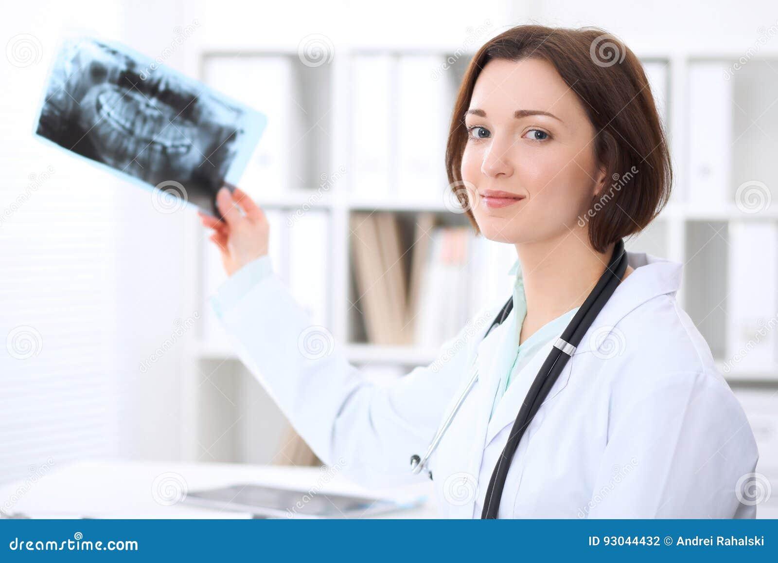 De jonge donkerbruine vrouwelijke tandartszitting bij de lijst en onderzoekt tandröntgenstraal
