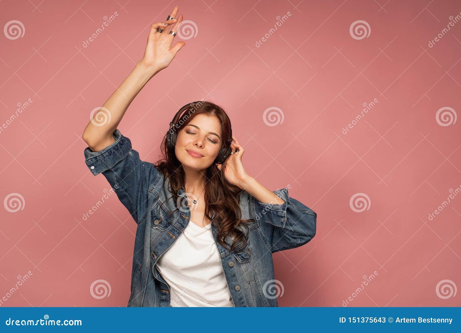 De jonge donkerharigedansen die van de muziek in haar hoofdtelefoons met haar ogen genieten sloten, roze achtergrond