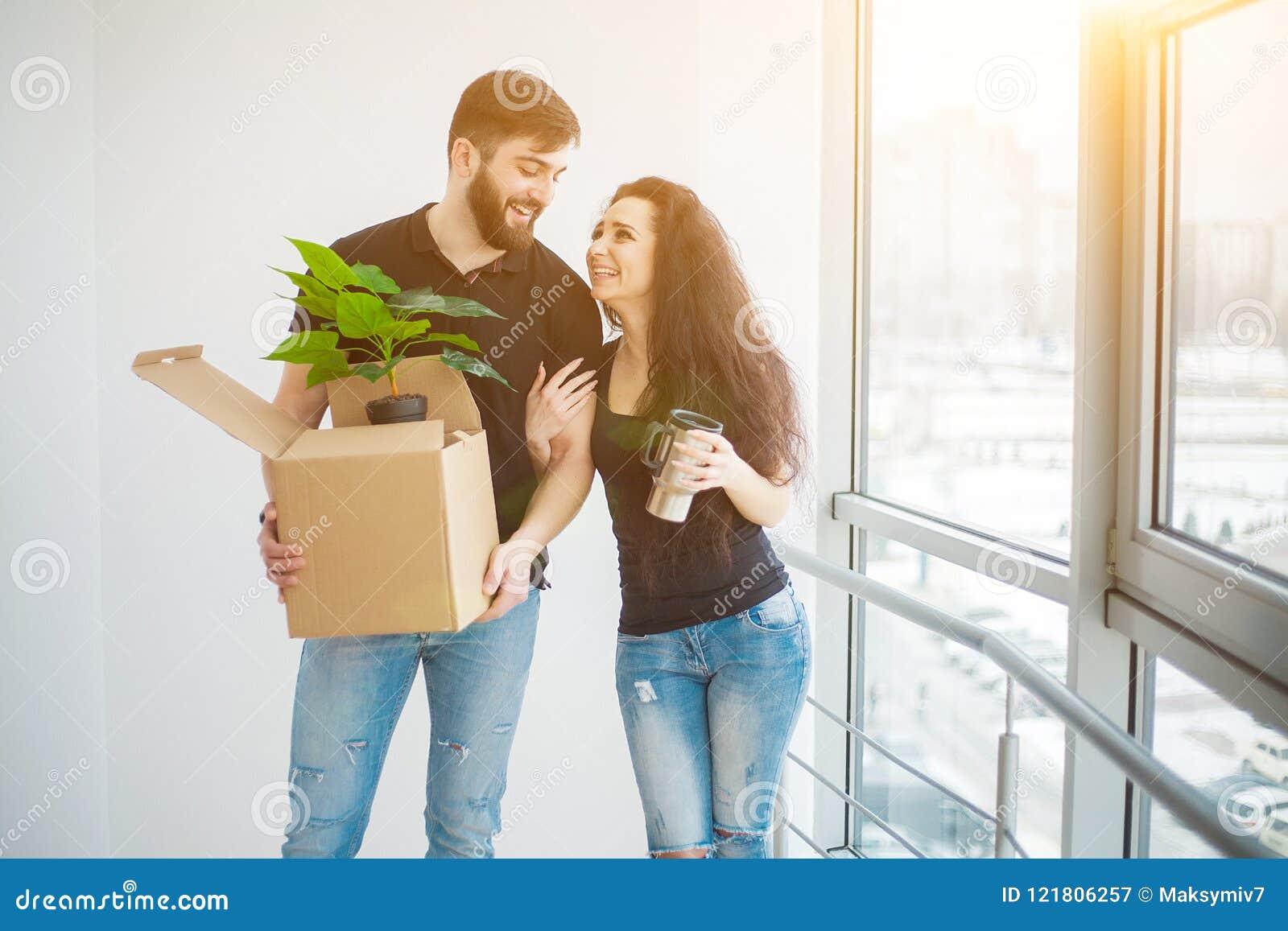 De jonge dozen van het paar uitpakkende karton bij nieuw huis Het bewegen van huis