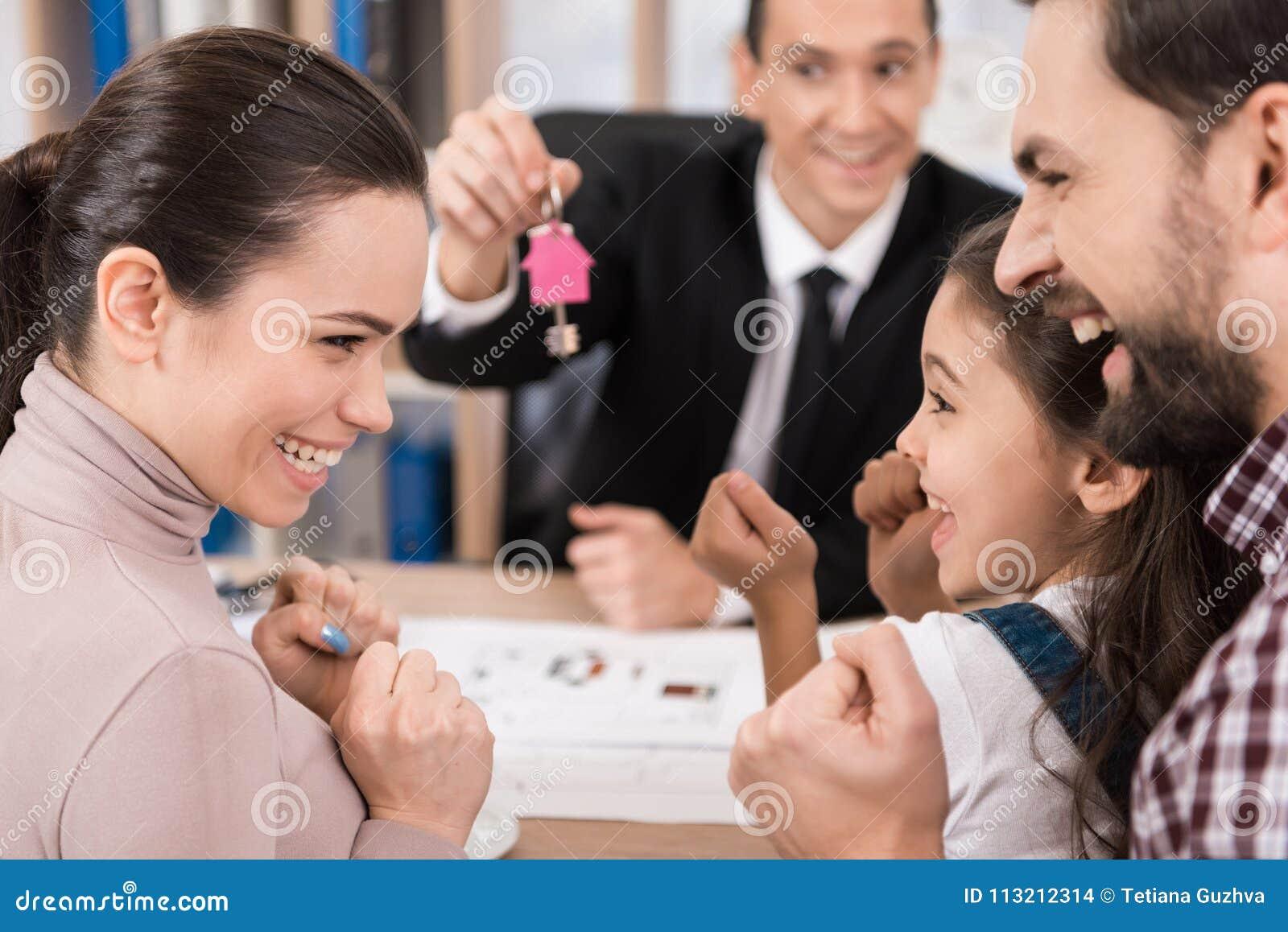 De jonge familie is gelukkig om nieuw huis in bureau van makelaar in onroerend goed te kopen Kopend huis Huis voor Verkoop