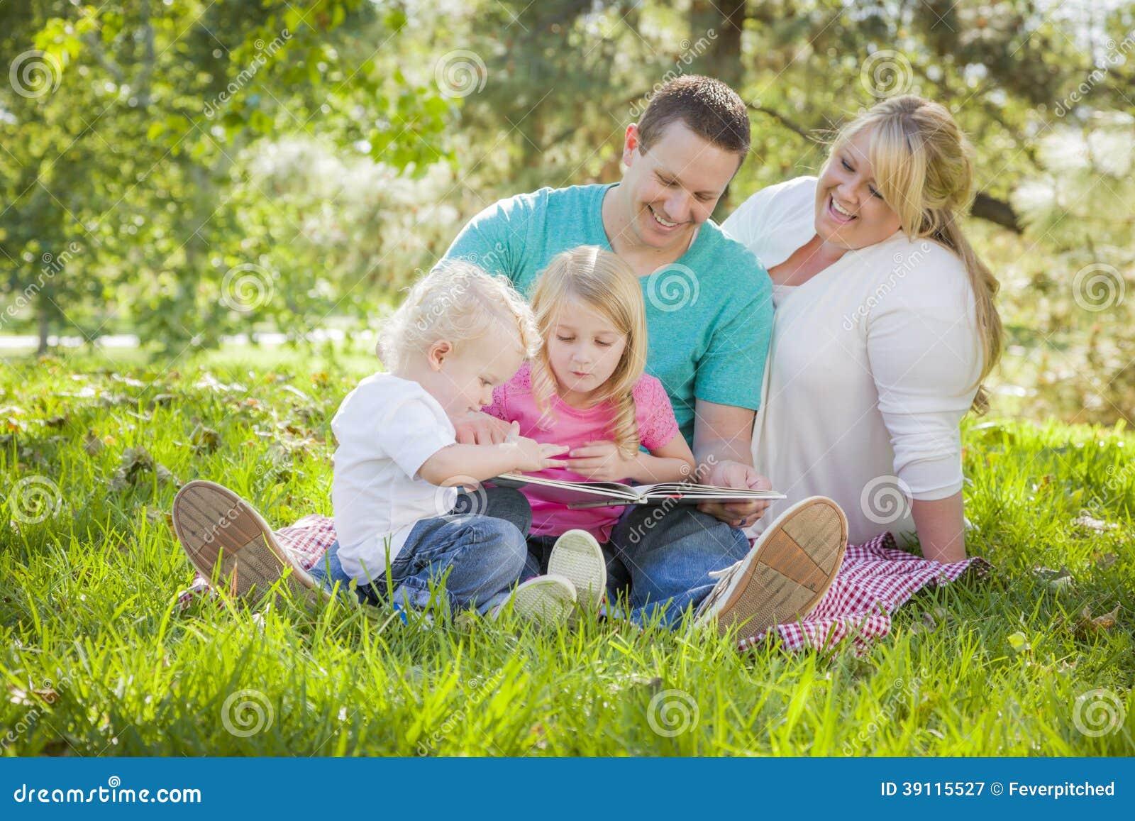 De jonge Familie geniet van lezend een Boek in het Park