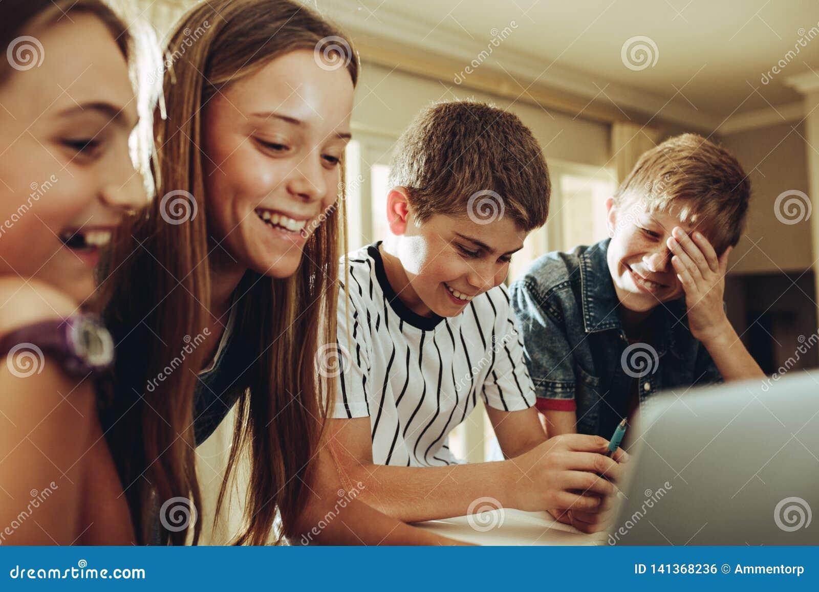 De jonge geitjes genieten van lerend met behulp van technologie