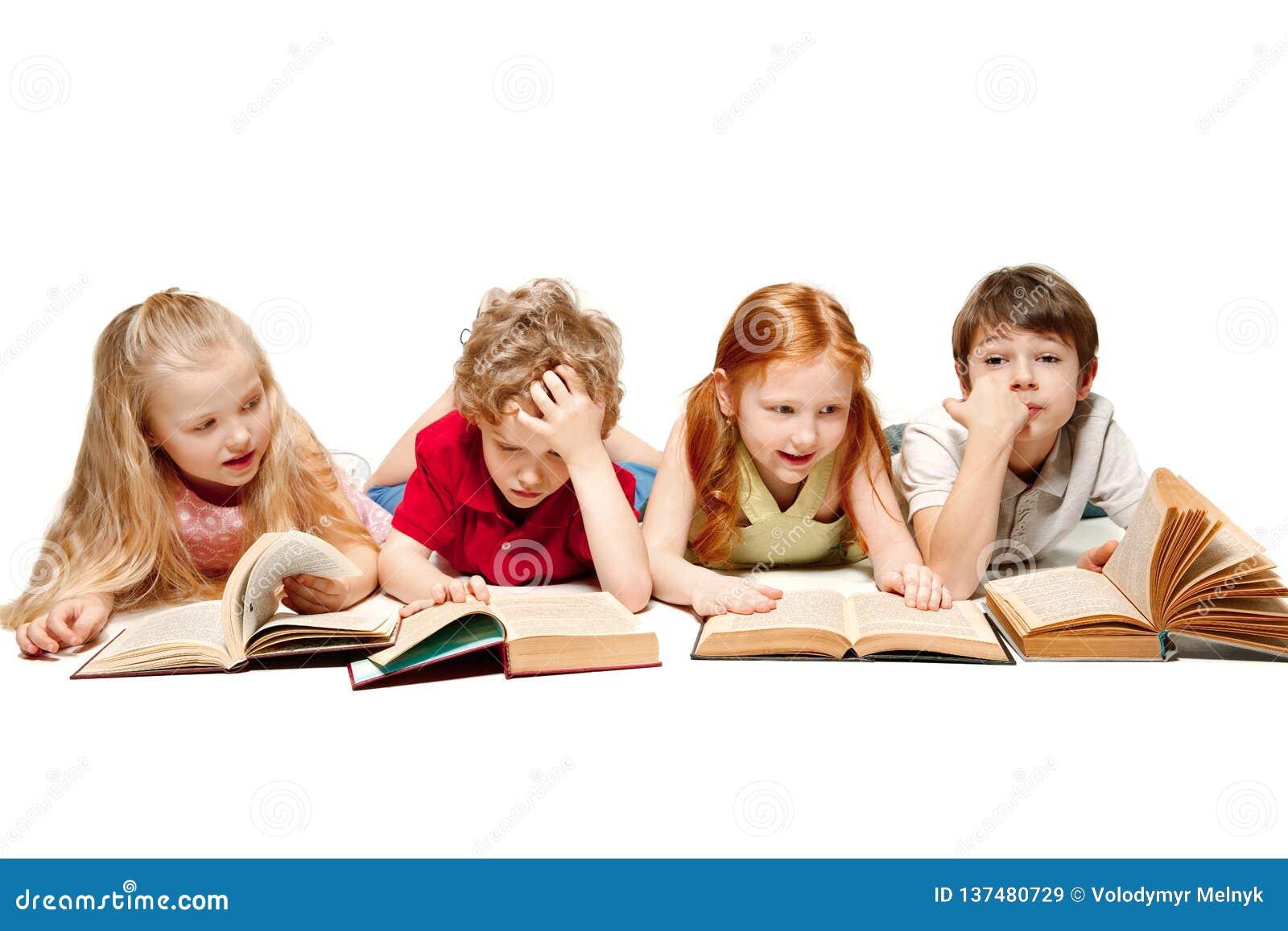 De de jonge geitjesjongen en meisjes die die met boeken leggen op wit worden geïsoleerd