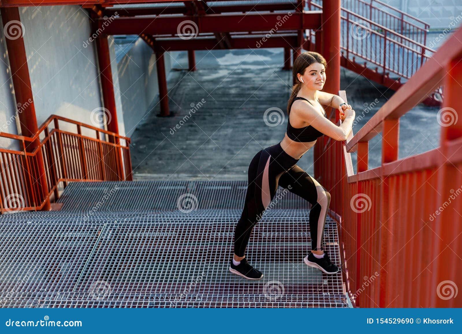 De jonge gelukkige atletische slanke mooie vrouw heeft een rust en status op treden na het doen van cardiointerval opleiding in z
