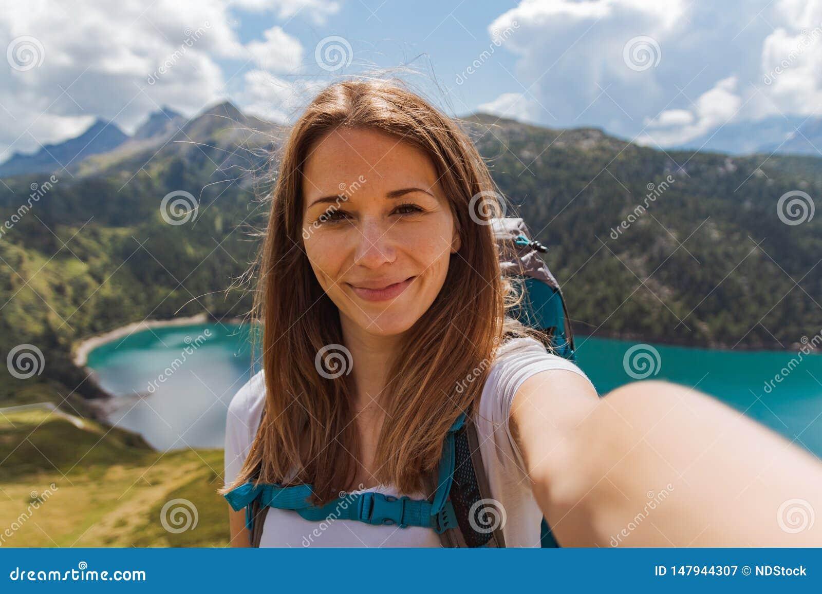 De jonge gelukkige vrouw neemt een selfie op de bovenkant van de berg in de Zwitserse alpen