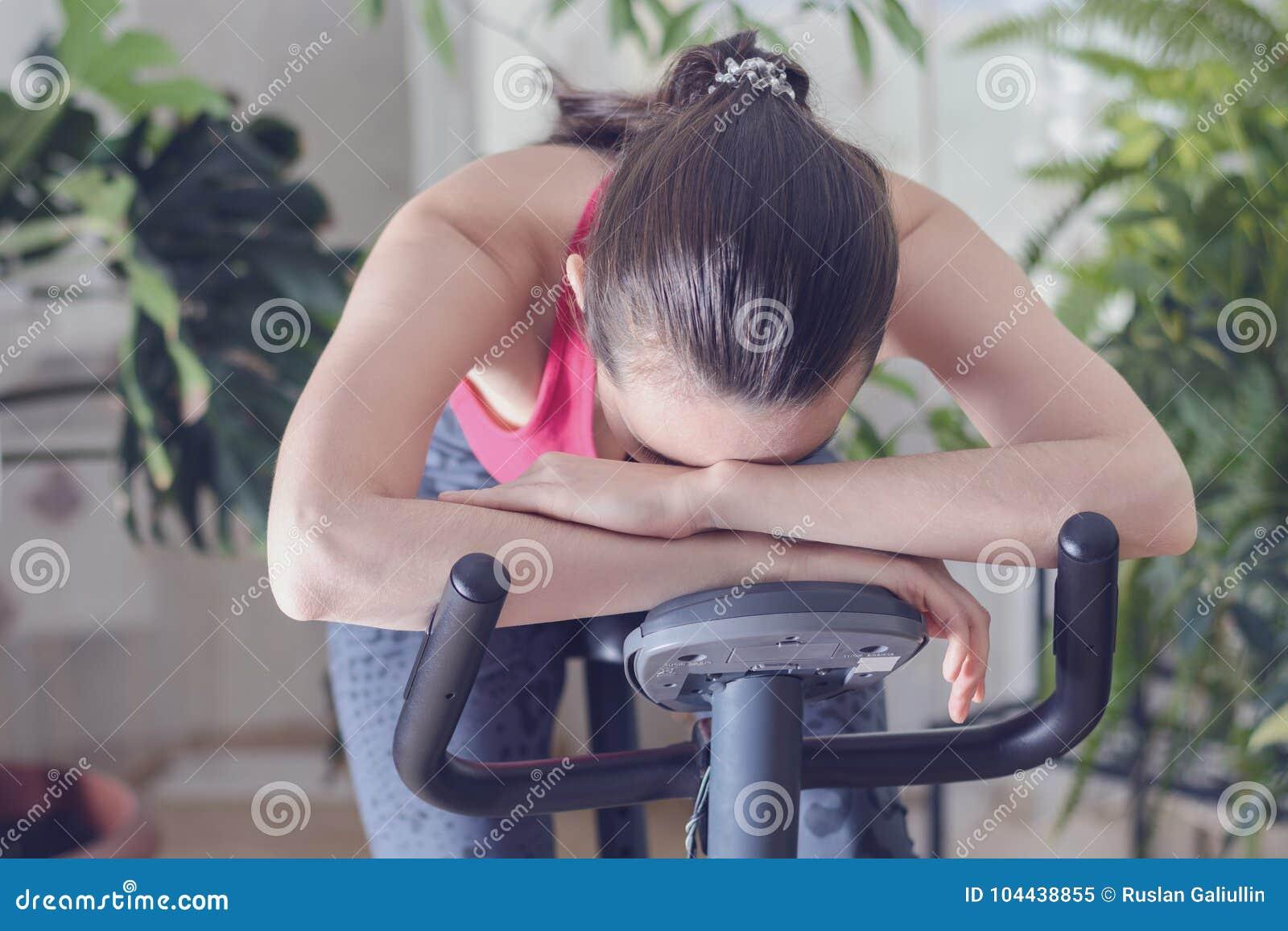 De jonge gezonde geschikte vrouw opleiding thuis op hometrainer tijdens werkt uitgeput gevoel uit en duizelig, verminderde zijn h