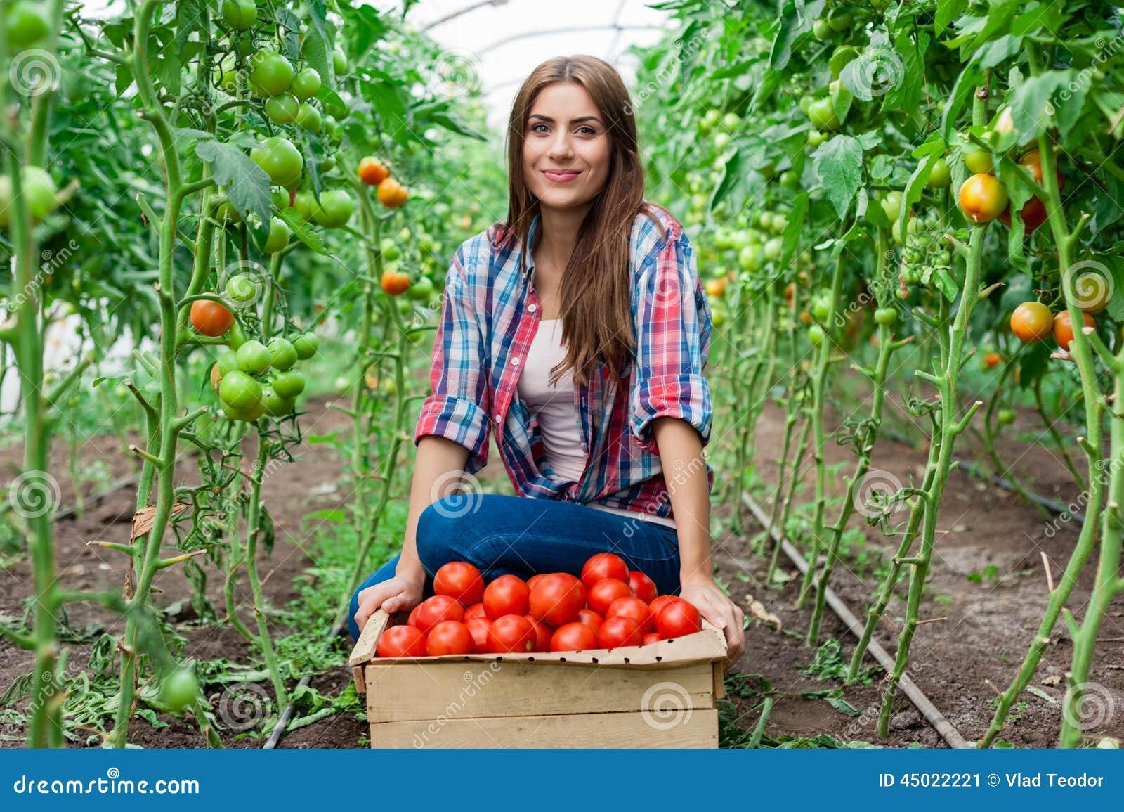 De jonge glimlachende arbeider van landbouwvrouwen