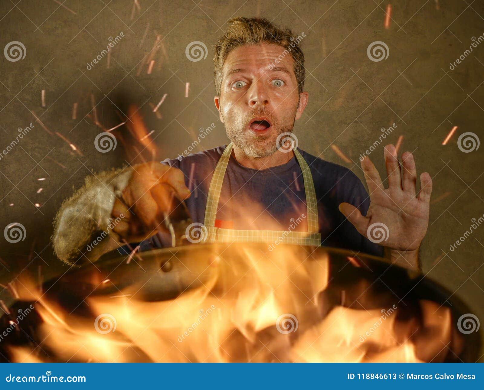 De jonge grappige en slordige mens van de huiskok met schort in de pan van de schokholding in brand die het voedsel in keukenramp
