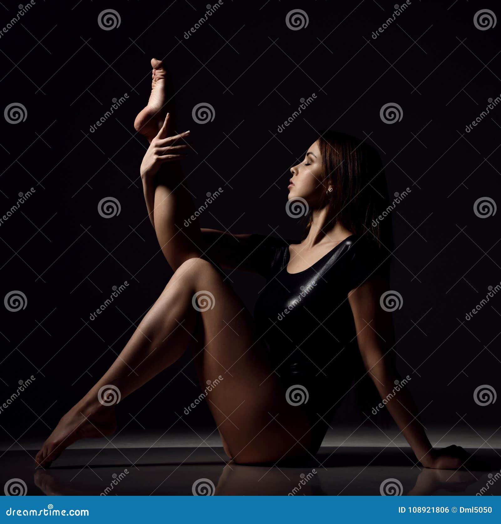 De jonge gymnastiek die van de sportvrouw uitrekkende fitness oefening doen bij donkere gymnastiek