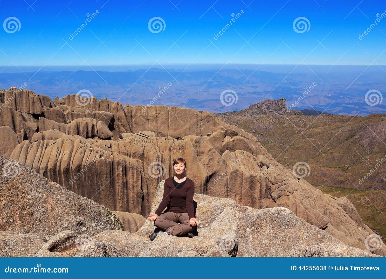 De jonge het glimlachen vrouwenzitting op rand van de bergyoga stelt