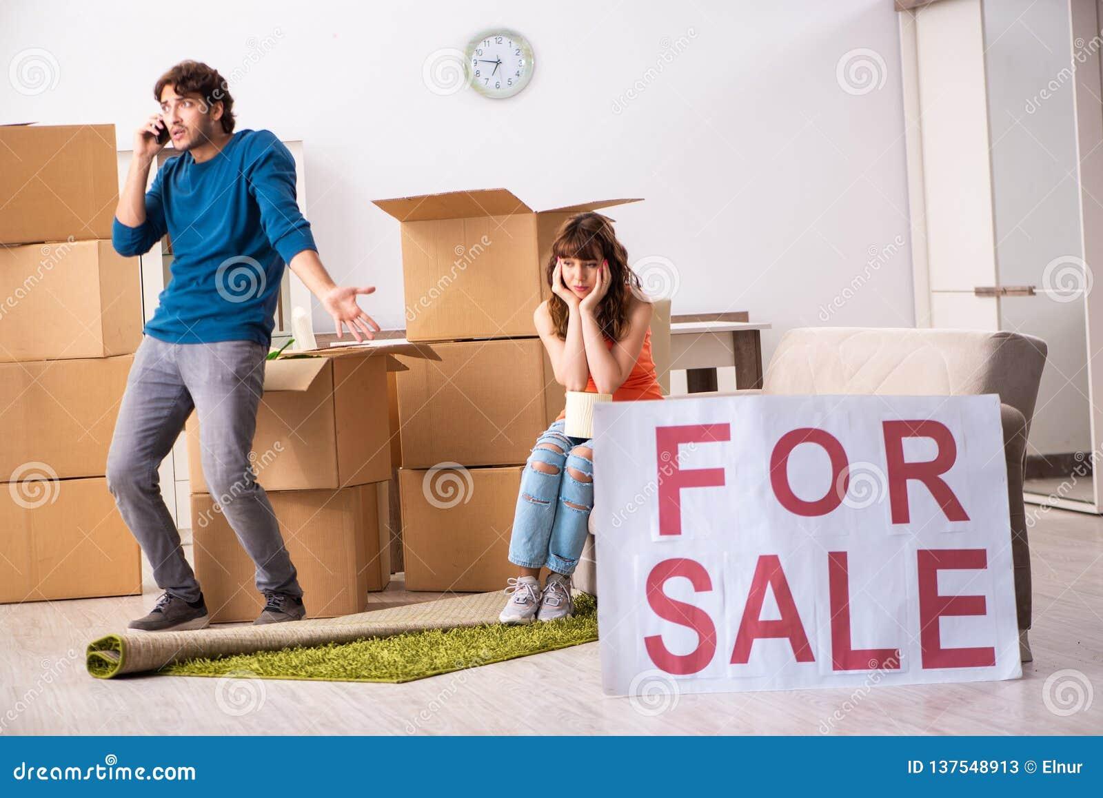 De jonge huis voor verkoop aanbieden en familie die zich uit bewegen