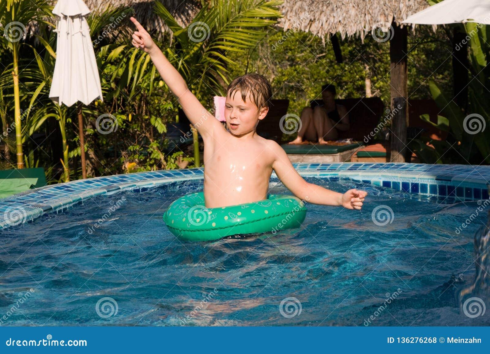 De jonge jongen in een floting band geniet van vers poolwater