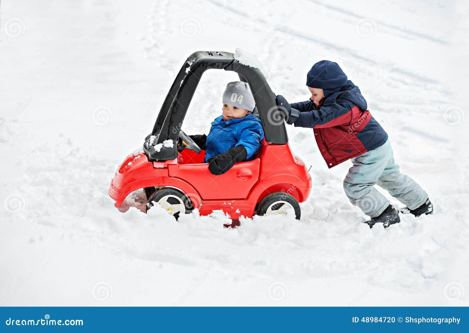 De jonge Jongen geeft een Duw aan de Auto van zijn die Broer in de Sneeuw wordt geplakt