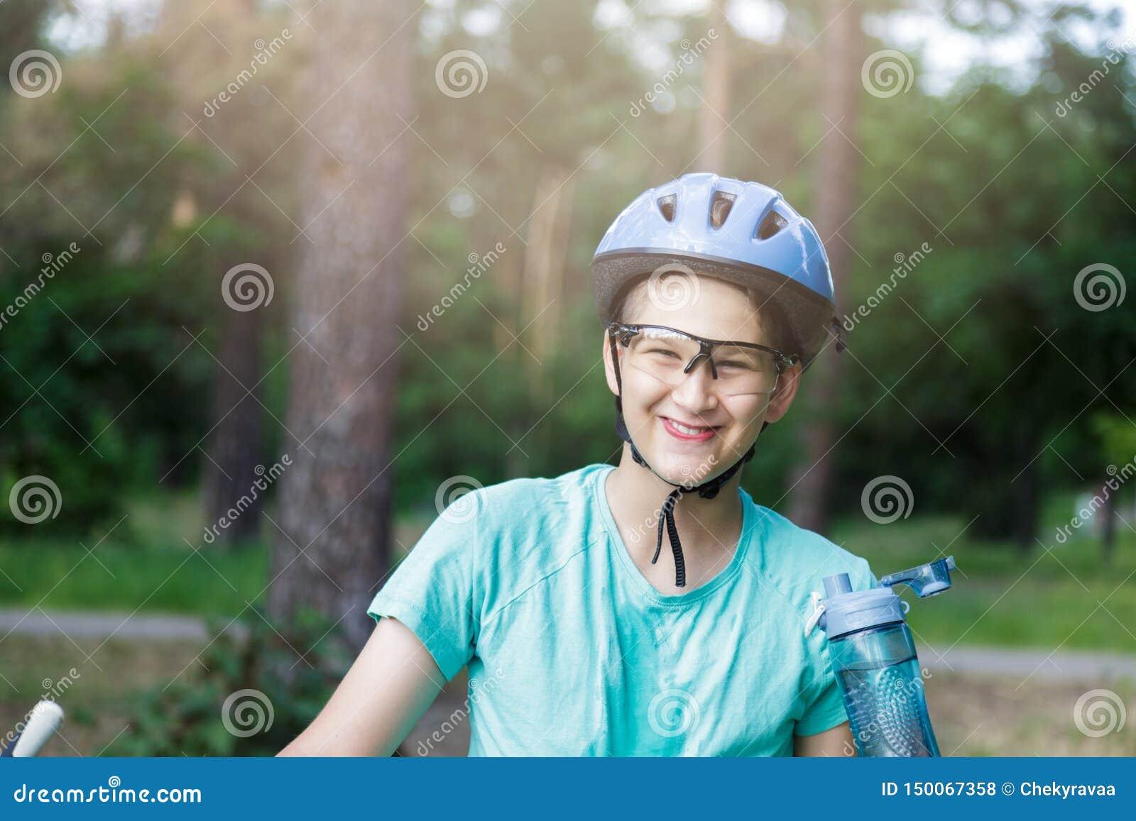 De jonge jongen in helm en groene t-shirtfietser drinkt water van fles in het park Glimlachende leuke Jongen op fiets in het bos